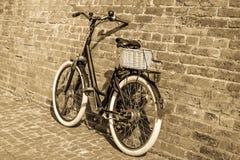 Rétro bicyclette noire de vintage avec le vieux mur de briques Images stock