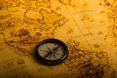 Rétro boussole sur la carte antique du monde Image stock
