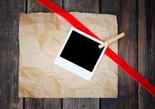 Rétro cadre vide de photo au-dessus de papier chiffonné Image stock