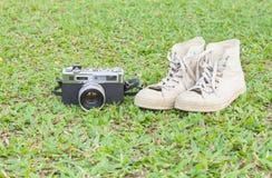 Rétro camerar et espadrilles sur l'herbe Photographie stock libre de droits
