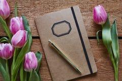 Rétro carnet entouré par les tulipes roses Photographie stock libre de droits
