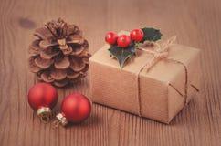 Rétro carte de Noël de style avec un boîte-cadeau et des baies de houx sur le fond en bois, modifié la tonalité Photo libre de droits