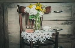 Rétro chaise avec des fleurs dans un vase, un vieux livre de prière et une tasse de thé Image libre de droits