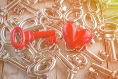 Rétro clé rouge avec le coeur rouge sur la table en bois Photo stock
