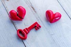 Rétro clé rouge avec le coeur rouge sur la table en bois blanche jpg Photos stock