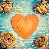 Rétro composition en style avec le coeur de feutre et les roses fanées Photographie stock libre de droits