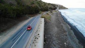 Rétro conduite rouge près de la mer sur la route Vue aérienne cinématographique banque de vidéos
