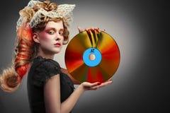 Rétro disque à laser de fixation de femme images stock