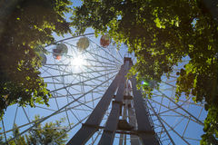 Rétro Ferris Wheel sur le ciel nuageux bleu et l'éruption chromosphérique Photos stock