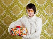 Rétro glaces de jeune homme de gratte-cul retenant le cadre de cadeau Photographie stock libre de droits