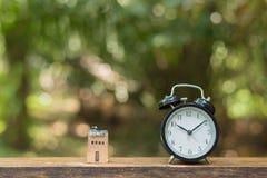 Rétro horloge avec la maison en bois minuscule Image stock