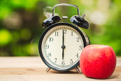 Rétro horloge avec la pomme de fruit de matin Photo stock
