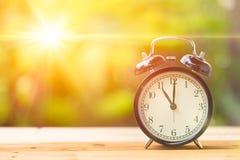 Rétro horloge de ` de 11 o et soleil de matin avec lumineux et la fusée Image libre de droits
