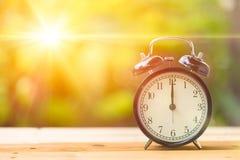 Rétro horloge de ` de 12 o et soleil de matin avec lumineux et la fusée Photos stock