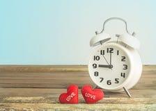 Rétro horloge et coeurs sur le fond en bois et bleu Image libre de droits