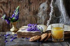 Rétro livre et verre de jus d'orange dans le matin Photographie stock libre de droits