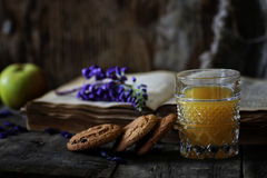 Rétro livre et verre de jus d'orange dans le matin Image stock