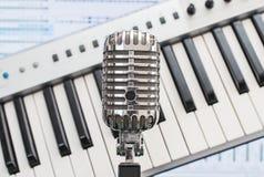 Rétro microphone au-dessus de piano photographie stock