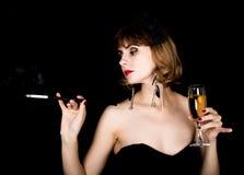 Rétro modèle femelle de beauté avec le maquillage professionnel tenant l'embouchure et le verre de champagne femme de vintage de  photographie stock libre de droits