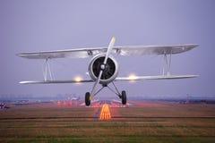 Rétro mouche plate au-dessus de piste de décollage d'aéroport au crépuscule Images stock