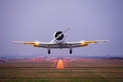 Rétro mouche plate au-dessus de piste de décollage d'aéroport au crépuscule Image stock