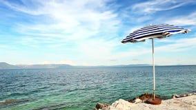 Rétro parapluie de style de seule plage sur le rivage croate banque de vidéos