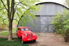 Rétro petite voiture rouge de vintage se tenant dans le jardin pendant l'été Photos stock