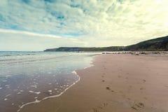 Rétro plage avec la baie de Cayton de scène d'empreintes de pas Photographie stock