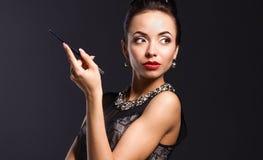 Rétro portrait de femme, se tenant sur le fond noir Photo stock