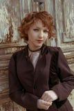 Rétro portrait des femmes d'une chevelure rouges à l'arrière-plan en bois obsolète d'agains de manteau de vintage Images libres de droits