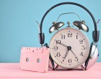 Rétro réveil avec les écouteurs et la cassette sonore sur la table en bois sur le fond en pastel, l'espace de copie image libre de droits