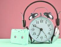 Rétro réveil avec les écouteurs et la cassette sonore sur la table en bois sur le fond en pastel, l'espace de copie photo libre de droits