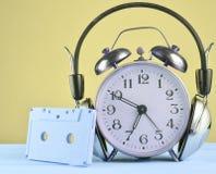Rétro réveil avec les écouteurs et la cassette sonore sur la table en bois sur le fond en pastel, l'espace de copie images stock