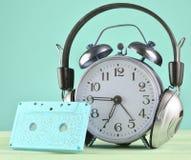 Rétro réveil avec les écouteurs et la cassette sonore sur la table en bois sur le fond en pastel, l'espace de copie photographie stock libre de droits