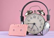 Rétro réveil avec les écouteurs et la cassette sonore sur la table en bois sur le fond en pastel, spac de copie photo stock