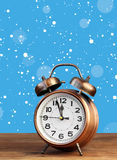 Rétro réveil en bronze à l'horloge de ` de douze o parmi la neige de vol Image libre de droits