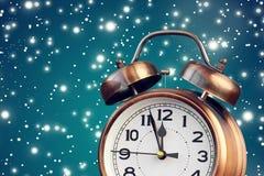 Rétro réveil en bronze à l'horloge de ` de douze o parmi la neige de vol Photo stock