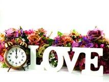 Rétro réveil et amour avec des fleurs sur le fond blanc Image libre de droits