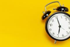 Rétro réveil noir sur l'espace étendu plat jaune de copie de vue supérieure de fond Fond de Minimalistic, concept de temps, date- photo stock