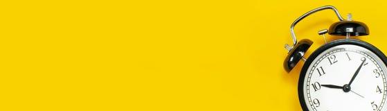 Rétro réveil noir sur l'espace étendu plat jaune de copie de vue supérieure de fond Fond de Minimalistic, concept de temps, date- image stock