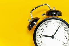 Rétro réveil noir sur l'espace étendu plat jaune de copie de vue supérieure de fond Fond de Minimalistic, concept de temps, date- photos stock