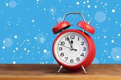 Rétro réveil rouge à l'horloge de ` de douze o parmi la neige de vol Photo libre de droits