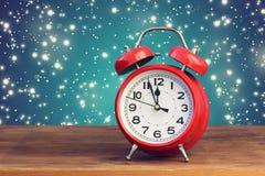 Rétro réveil rouge douze à l'o& x27 ; horloge parmi la neige de vol Photos libres de droits