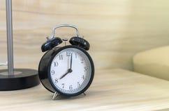 Rétro réveil sur la table près du lit au matin Images stock