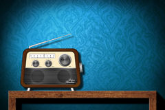 Rétro radio sur la table en bois avec le papier peint bleu Photographie stock libre de droits