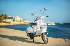 Rétro scooter blanc sur la plage Remblai touristique en Grèce Image libre de droits
