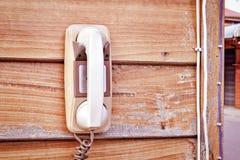 Rétro téléphone blanc sur le mur en bois Photo stock