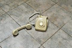 Rétro téléphone rotatoire sur un plancher carrelé image libre de droits