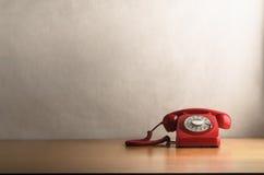 Rétro téléphone rouge sur le bureau en bois léger de placage Photo stock