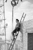 Rétro travailleur de la construction montant une échelle tout en travaillant au Photo libre de droits